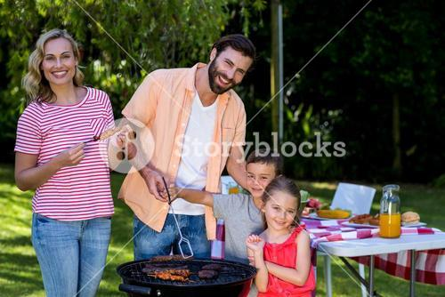 Family cooking food on barbecue grill at yard