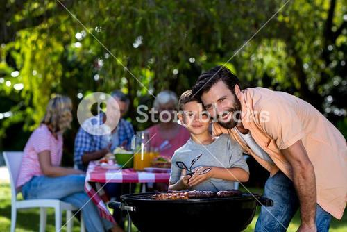 Smiling father with son by barbecue grill in yard