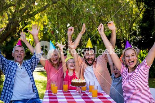 Family with arms raised enjoying birthday at yard