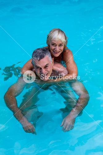 Happy senior couple enjoying in swimming pool