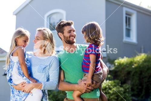 Parents carrying children in yard