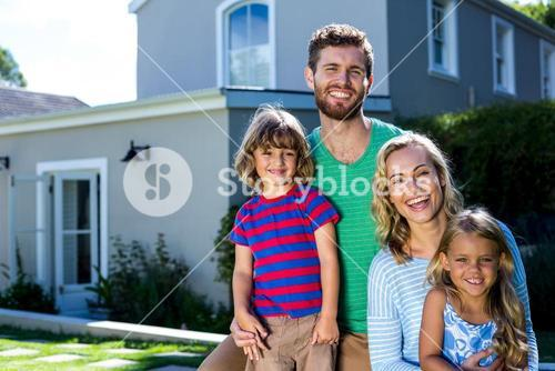 Cheerful family against house