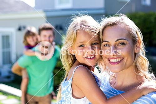 Smiling parents carrying children