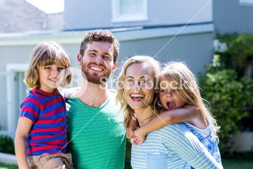 Smiling family standing against house