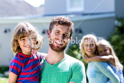 Happy family standing against house