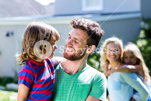 Parent carrying children in yard