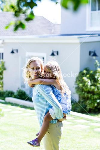 Mother piggy-backing daughter in yard