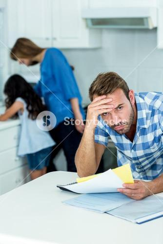 Worried father holding bills at home