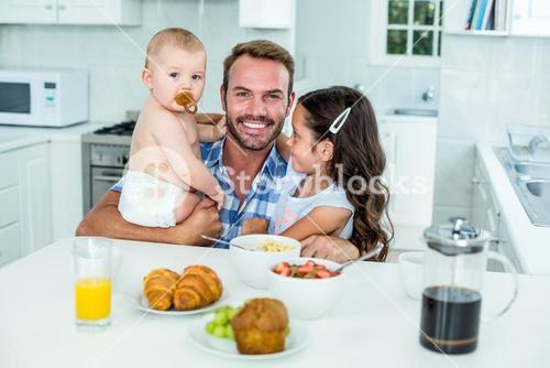 Smiling man with two children having breakfast in kitchen