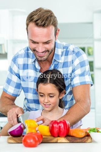 Father assisting daughter in chopping vegetables