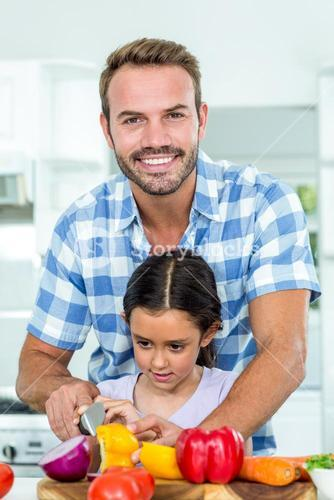 Father assisting daughter in cutting vegetables at home