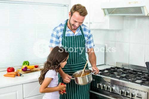 Father and daughter preparing food in kitchen