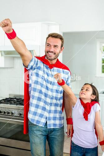 Father and daughter in superhero costume with hand raised