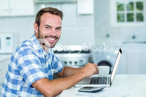 Happy handsome man using laptop at table in kitchen