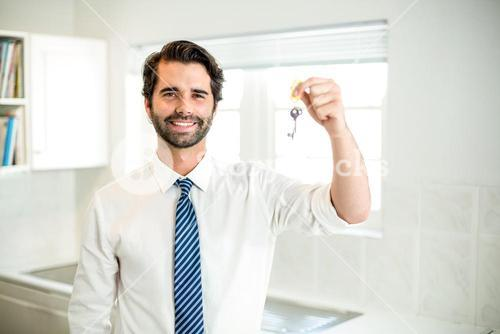 Confident businessman holding house key at home