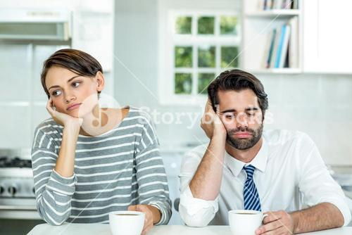 Upset couple with coffee cup sitting at table