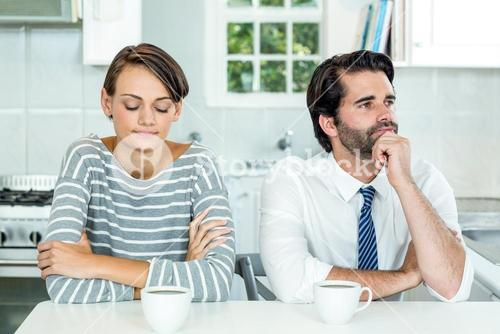 Unhappy couple sitting at table in kitchen
