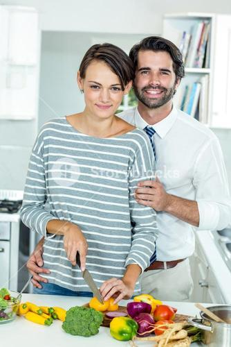Happy couple cutting vegetables at table in kitchen