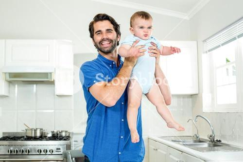 Father playing with son by kitchen counter at home