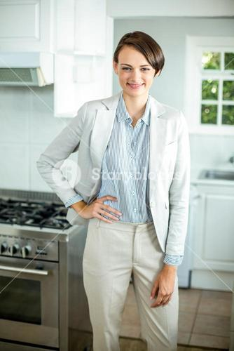 Businesswoman standing with hand on hip in kitchen