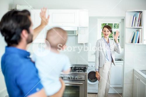 Man waving at wife while carrying son