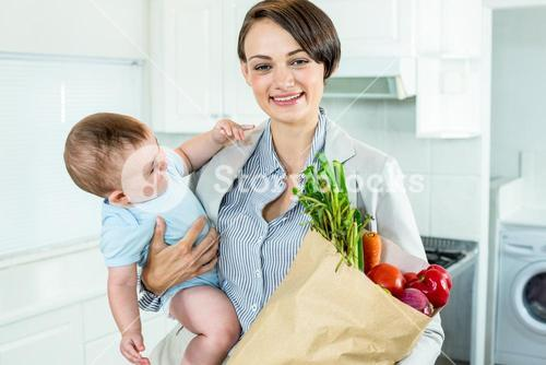 Businesswoman carrying son while holding vegetables