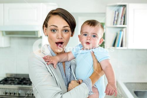 Surprised mother carrying son in kitchen at home