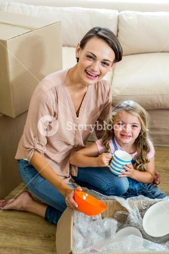Mother and daughter unpacking box in new house