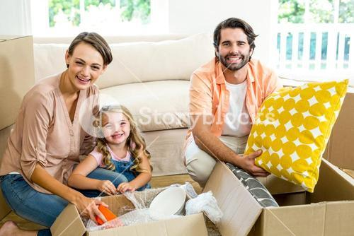Happy family unpacking boxes in new house