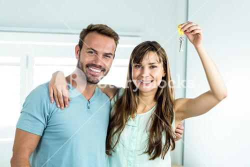 Couple smiling while showing house key
