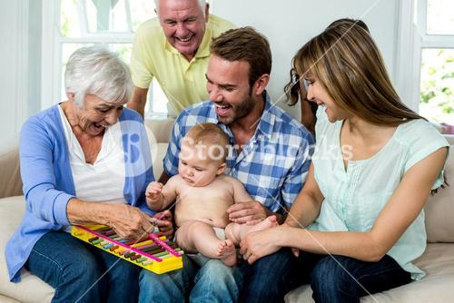 Multi-generation family showing xylophone to baby boy