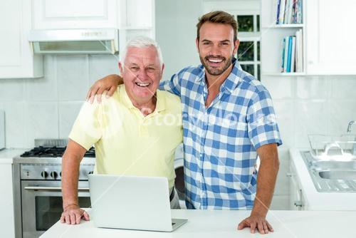Man standing with father by laptop at table in kitchen