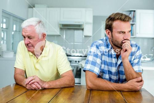 Tensed father and son sitting at table in kitchen