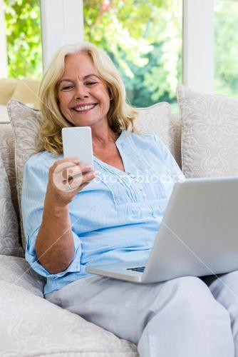 Senior woman using mobile phone while working on laptop at home
