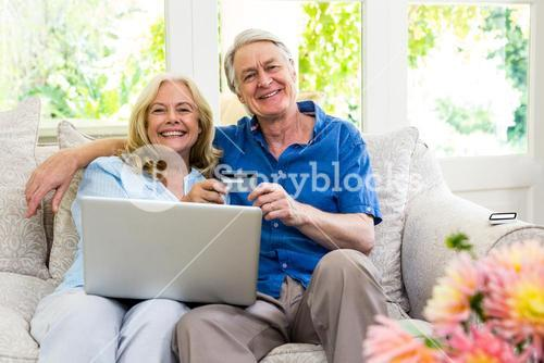 Happy senior couple holding smart card with laptop while sitting at home