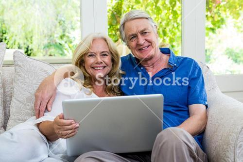 Portrait of happy senior couple with laptop at home