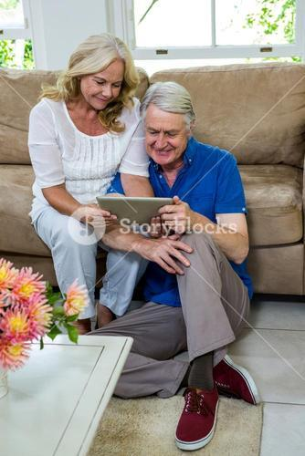 High angle view of senior couple using digital tablet in living room
