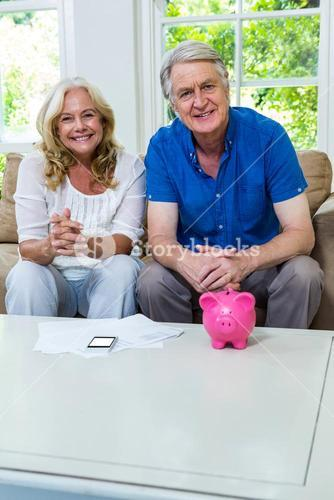 Happy senior couple sitting with piggi bank in living room at home