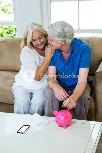 Senior couple putting coin in piggi bank while sitting at home