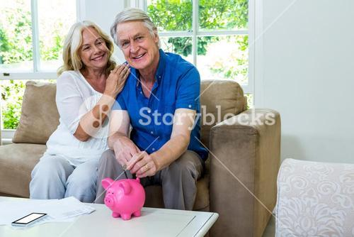 Smiling senior couple putting coin in piggi bank at home