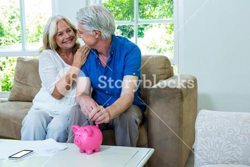 Cheerful senior couple putting coin in piggi bank at home