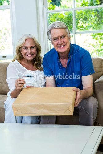 Happy senior couple holding parcel with smart card at home