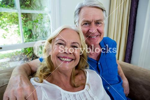 Smiling senior couple sitting in living room at home