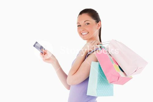 Attractive woman with a credit card holding shopping bags while standing