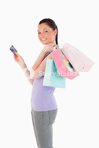 Beautiful woman with a credit card holding shopping bags while standing
