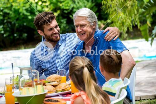 Father and son with children at dinning table in lawn