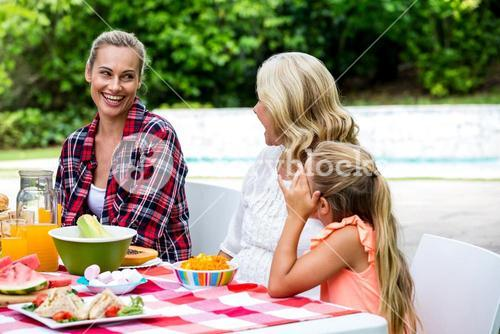 Smiling woman taking to mother and daughter at table