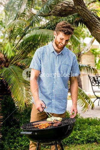 Happy man preparing food on barbecue grill