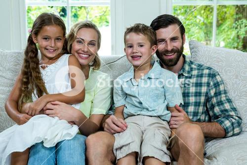Portrait of happy children with parents on sofa