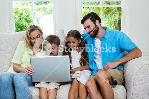 Smiling children with parents using laptop at home